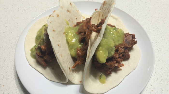 Three jackfruit brisket and guacamole tacos on a white plate