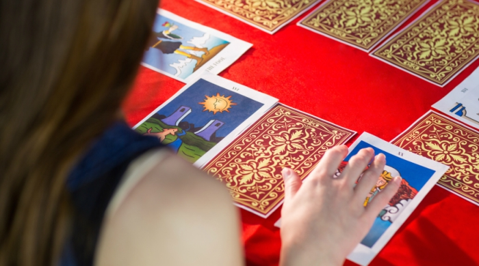 Brown haired girl reading tarot cards laid out on a red table cloth