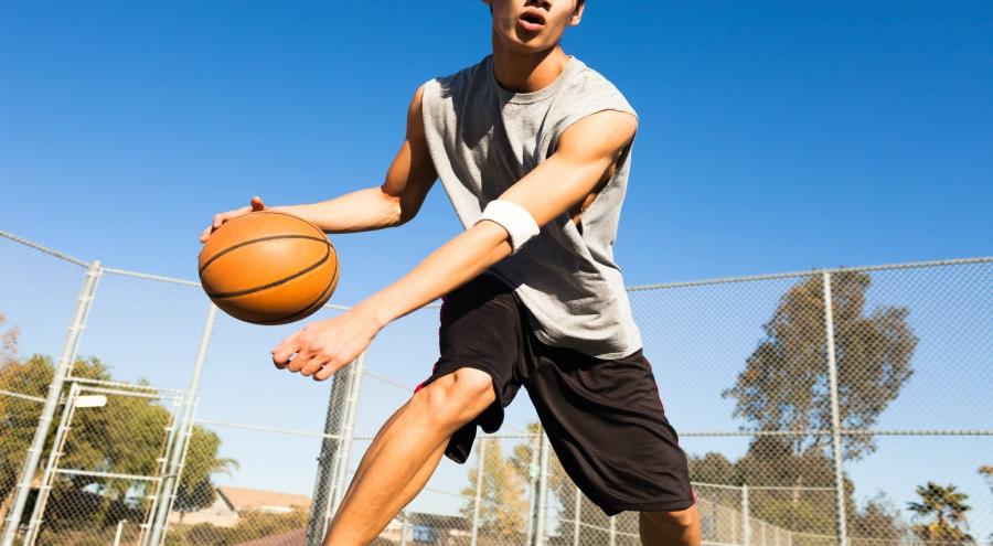 Teen boy playing basketball