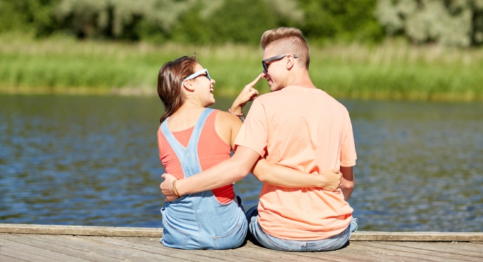cute couple flirts with arms around each other by the lake
