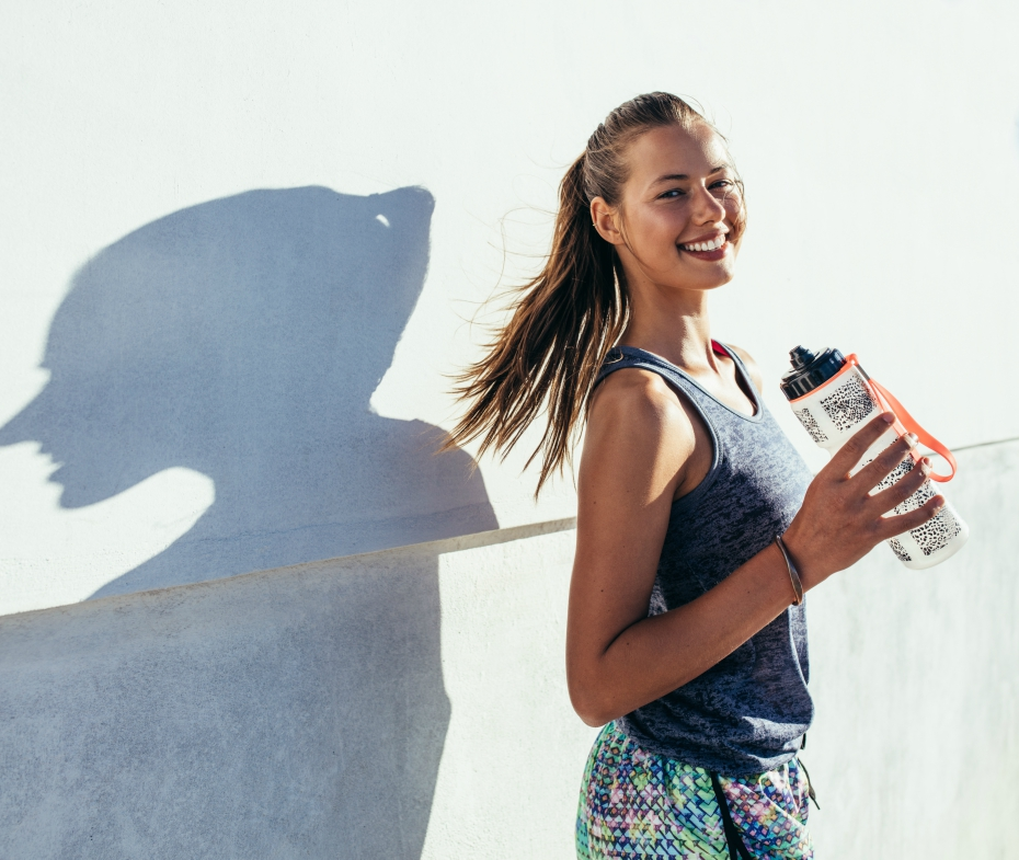 smiling girl holds water bottle while going for a run