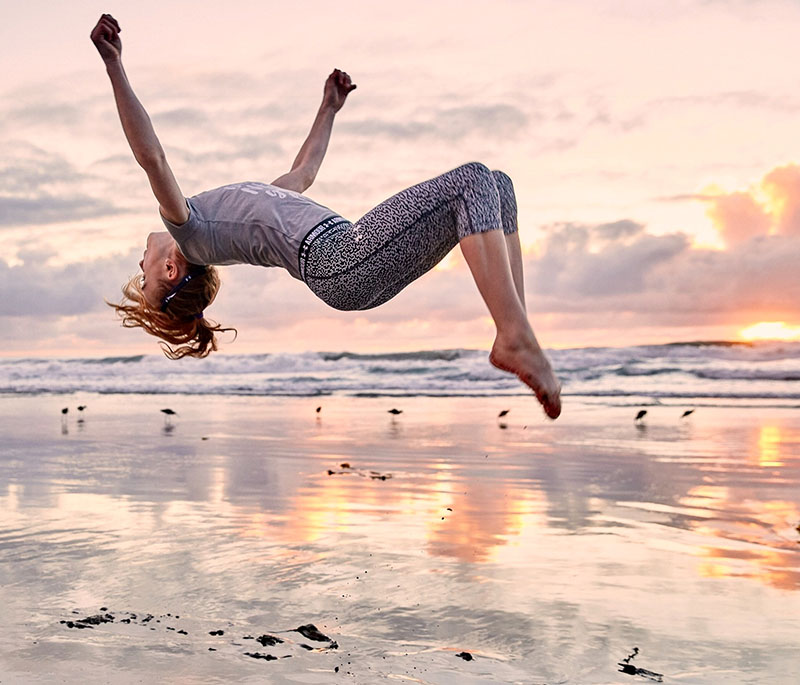 Girl doing a backflip on the beach