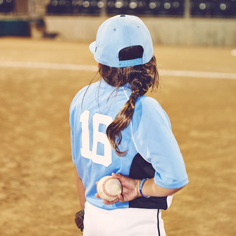 Photo of the back of a girl dressed in a baseball uniform