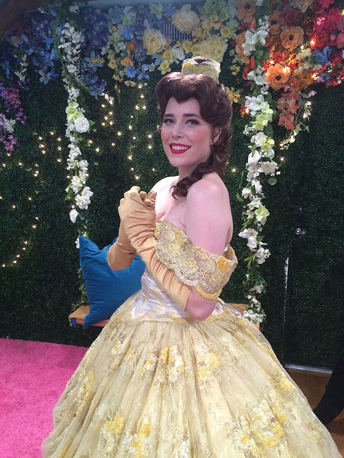 Girl dressed as Belle in front of a floral background