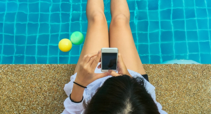 girl in pool plays with phone