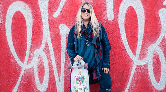 Picture of Cindy Whitehead holding a skateboard in front of a red wall