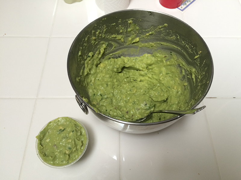 Guacamole in a large container next to Chipotle's guacamole in their smaller container