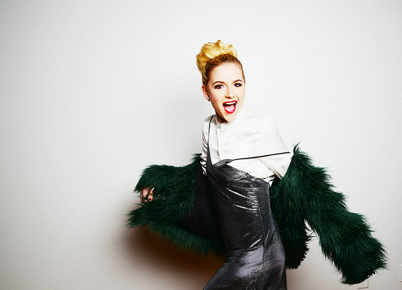 Pop artist Felicity wearing a green fur coat and smiling at the camera