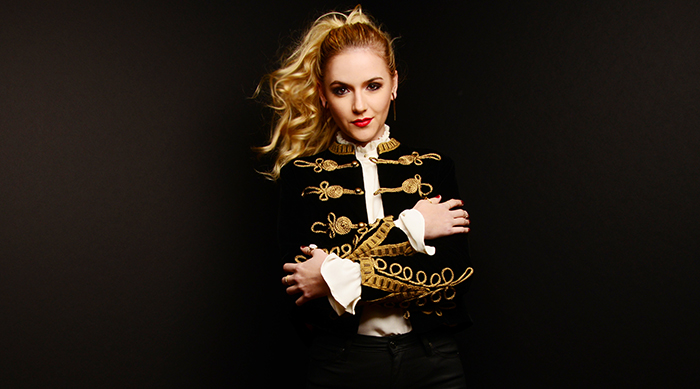 Pop artist Felicity crossing her arms in front of a black background