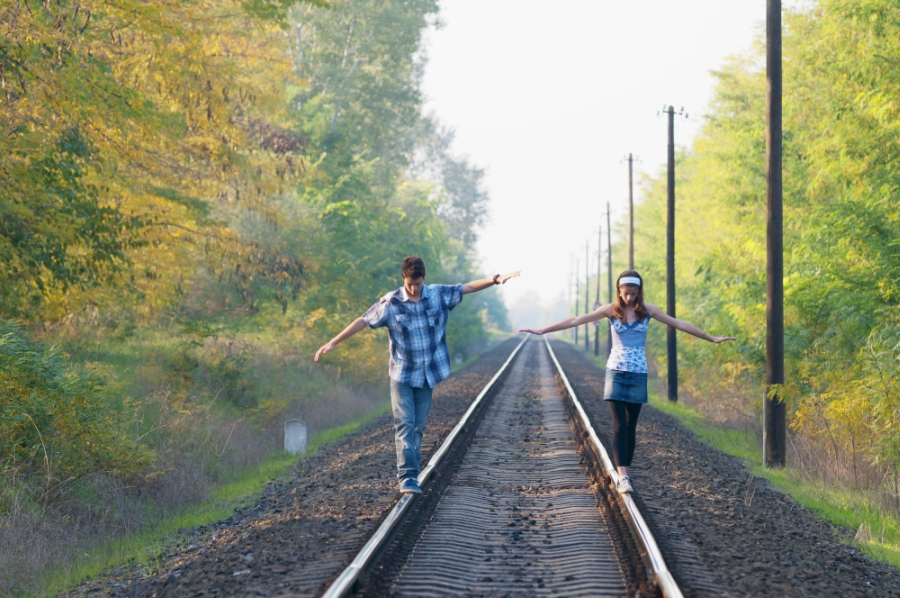 Girl and boy balancing on a railroad track