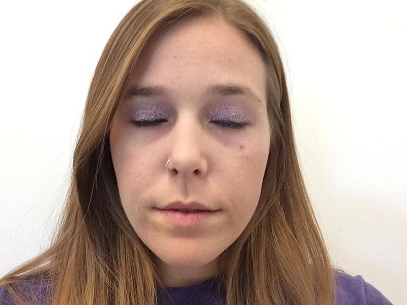 Blonde girl wearing purple glitter on her eyelids