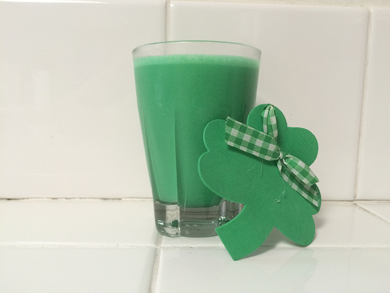 Homemade vegan Shamrock Shake next to a three-leaf clover