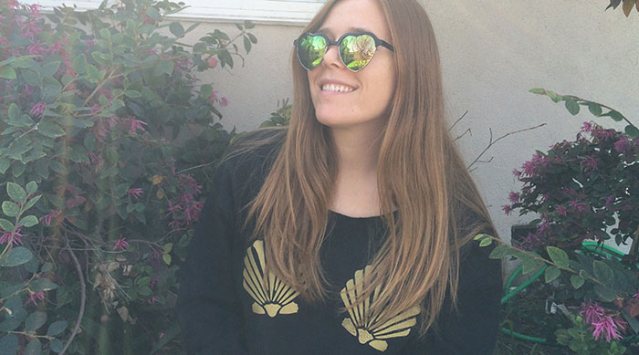 Girl wearing black sweatshirt with two gold seashells on the front of it