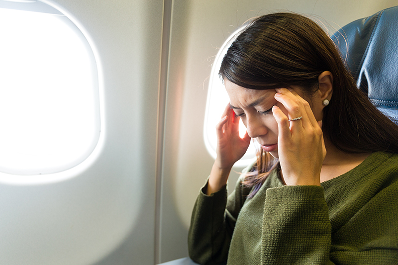 Woman with a migraine on a plane