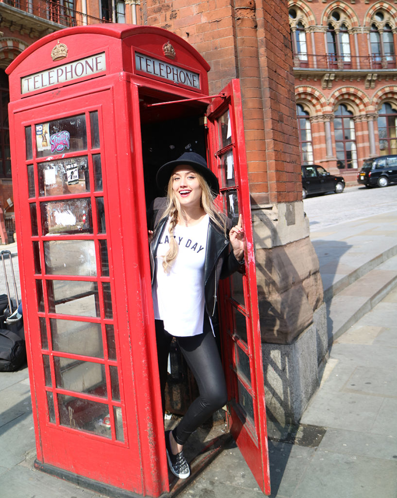 Naomi Kyle taking a photo in a London telephone booth
