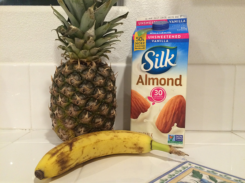 A pineapple, a banana and Silk almond milk on a kitchen counter