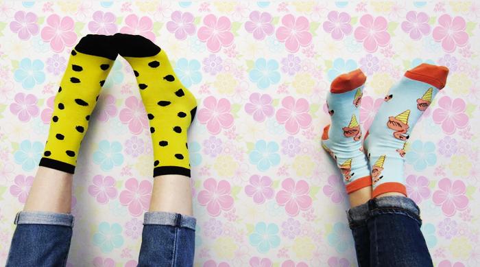 Girl wearing yellow socks with black polka dots and girl wearing blue socks with flamingos in ice cream cones on them
