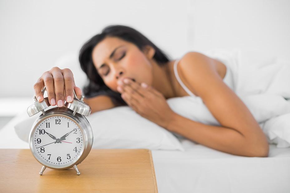 Sleepy yawning woman hitting alarm clock