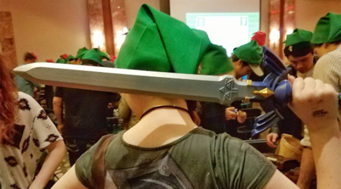 Girl wearing a green Link cap while holding the Master Sword from the Zelda-themed escape room behind her head