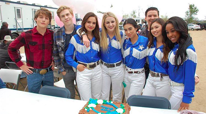 Bailee Madison, Chloe Lukasiak, Aidan Alexander, Froy Gutierrez and the rest of the cast of A Cowgirl's Story standing in front of a table