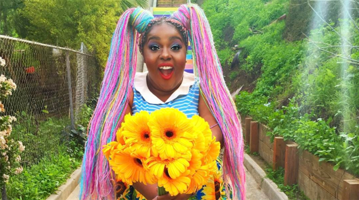 Amina Mucciolo holding sunflowers and smiling at the camera