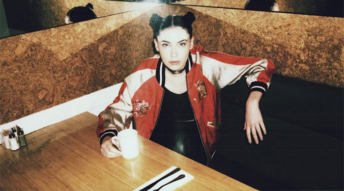 Bishop Briggs sitting in a booth in a restaurant drinking a cup of coffee