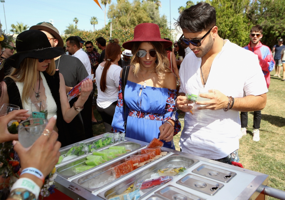 a guy and girl check out popsicles at a coachella party in the sun