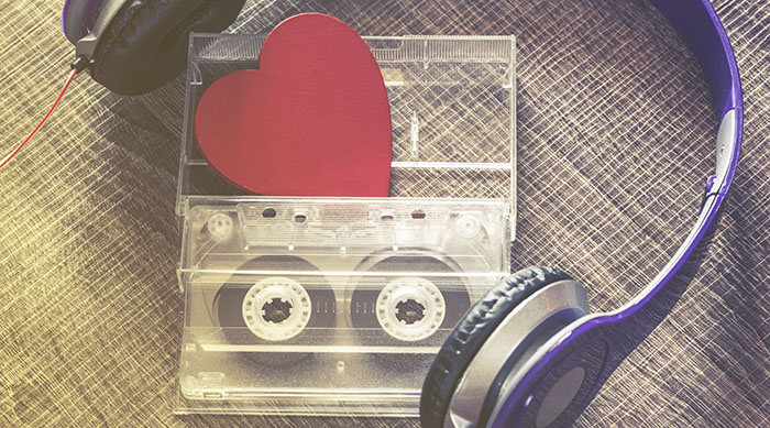 Cassette tape with a red heart on top of it surrounded by a pair of purple headphones