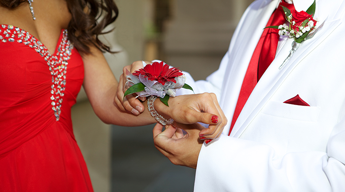 Guy in white tux putting a red rose corsage on a girl wearing a red dress for prom