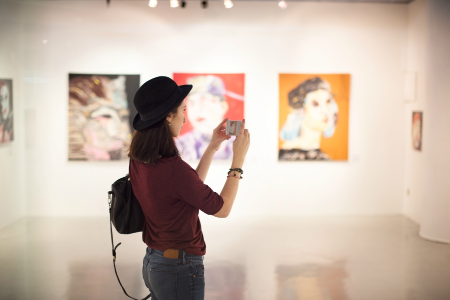 Girl taking pictures at an art exhibit
