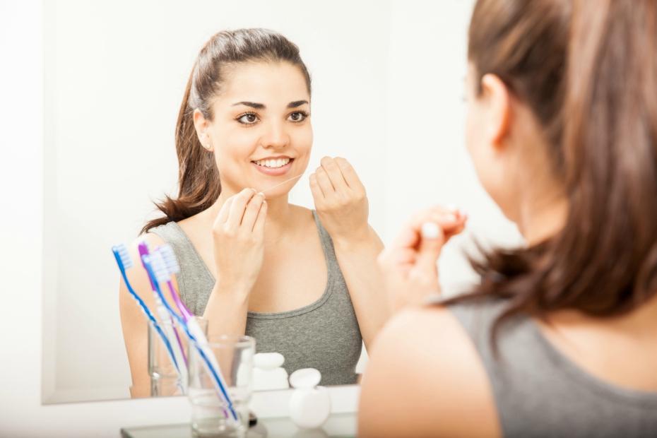 girl in front of mirror flosses her teeth