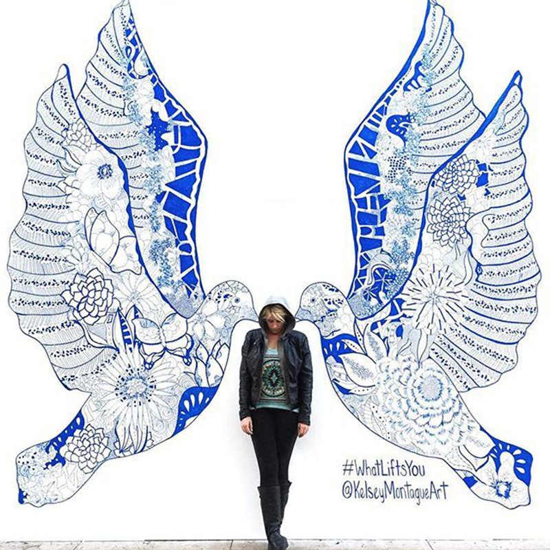 Girl posing in between a mural of two blue and white doves
