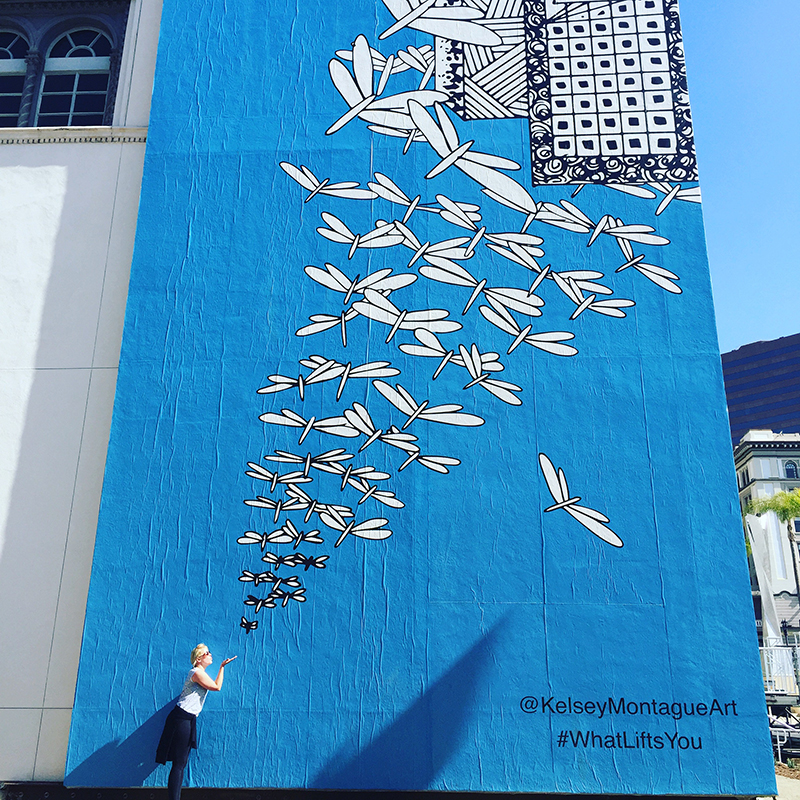 Mural of dragonflies by Kelsey Montague on a blue wall