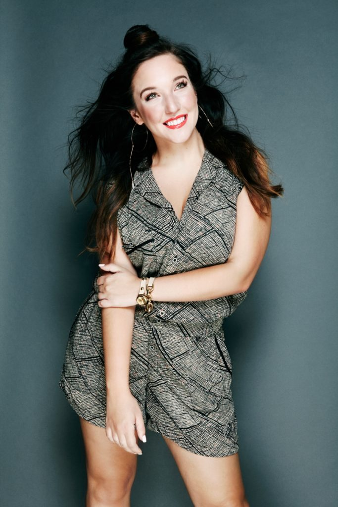 Gianna Martello wearing a romper and smiling in front of grey background