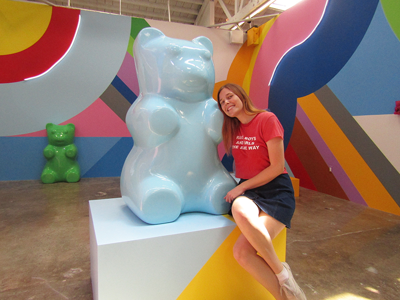 Girl hugging a giant blue gummy bear at the Museum of Ice Cream