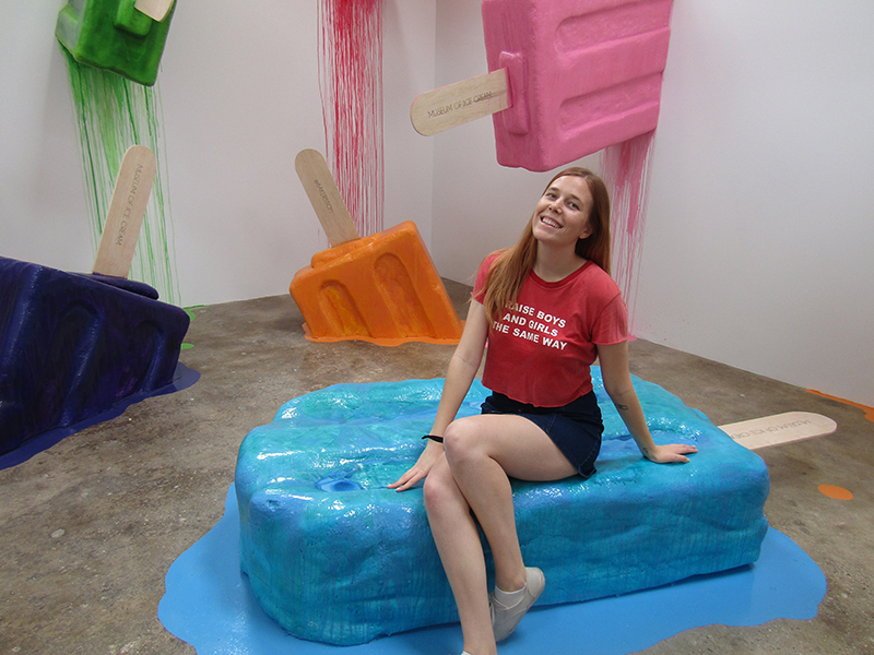Girl sitting on a giant melting popsicle in an exhibit at the Museum of Ice Cream