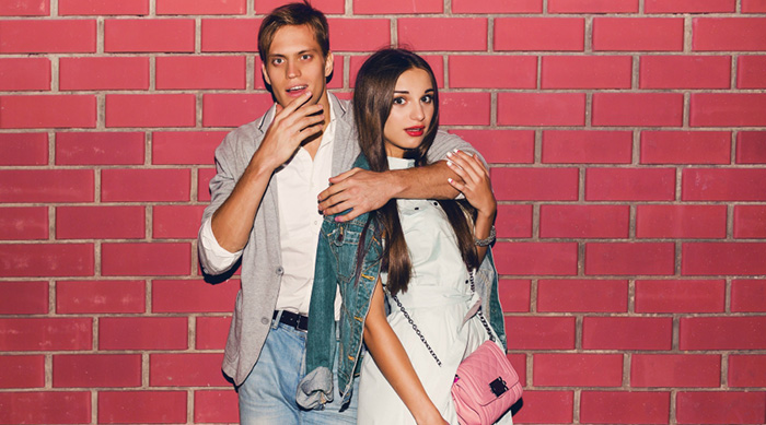 Girl and guy in front of a brick wall