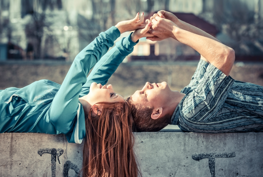 Girl and guy holding hands while laying down