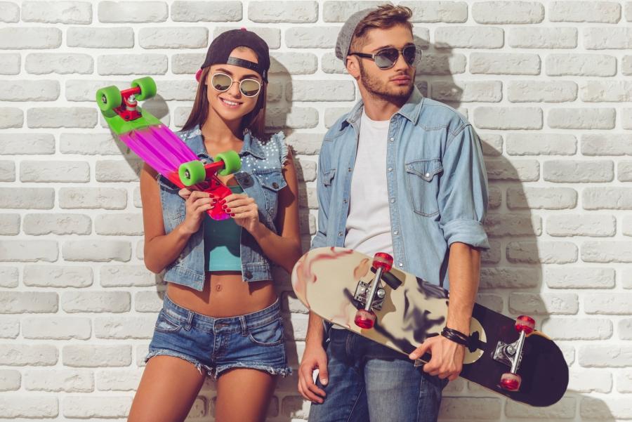 Teen girl and guy holding skateboards