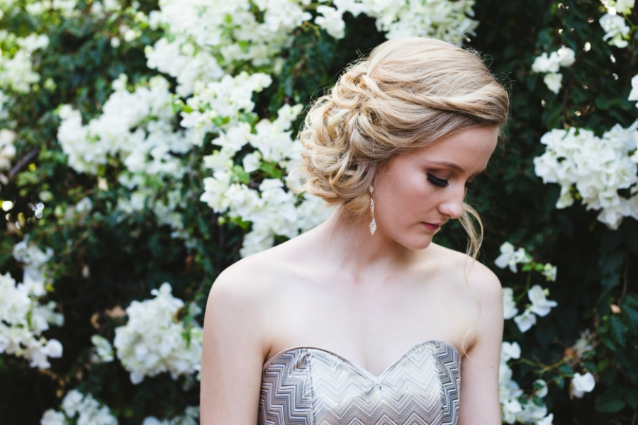 Blonde girl in a prom dress standing in front of flowers