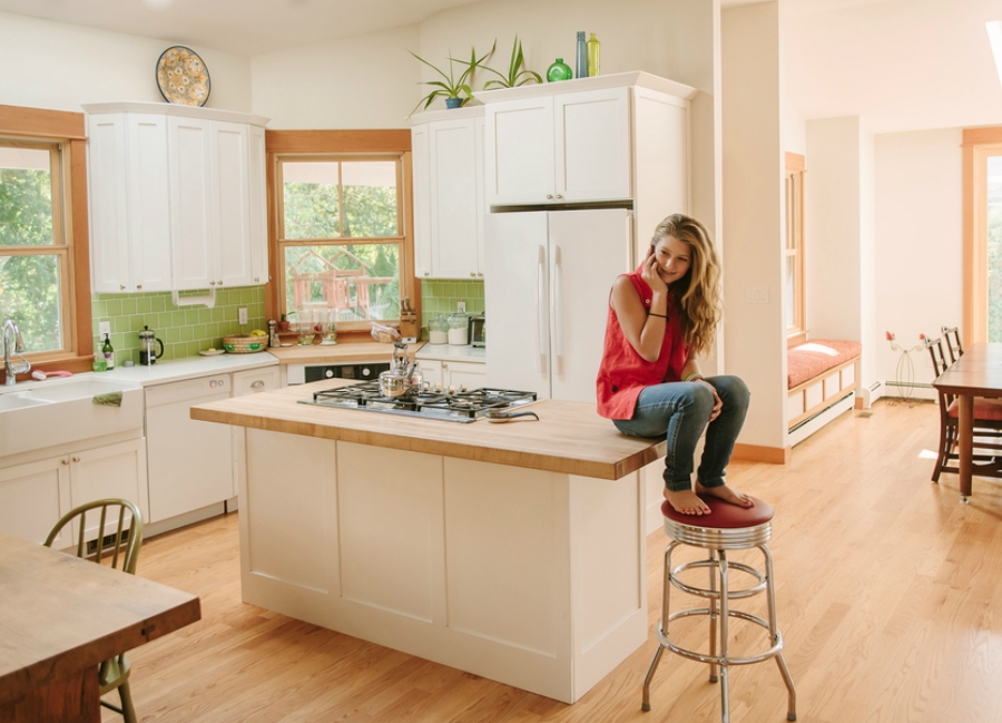 A girl in her kitchen talking on the phone