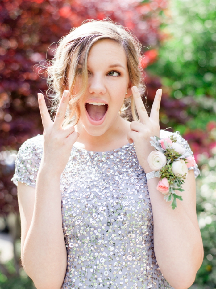 Girl throwing up peace sign in a prom dress