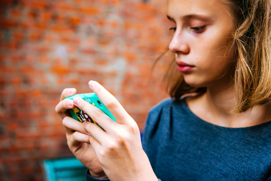 Girl texting in front of a brick wall