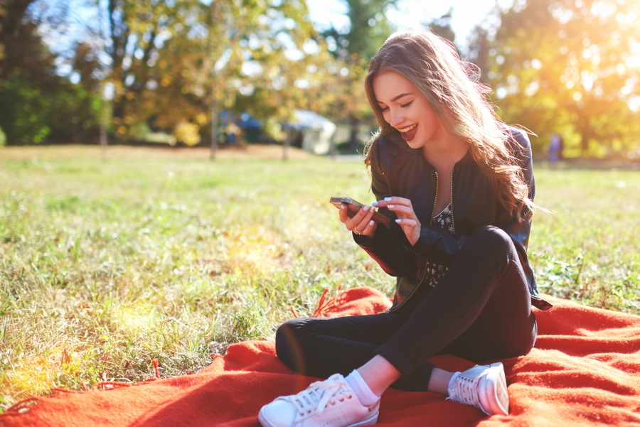 Girl texting outside on a red blanket