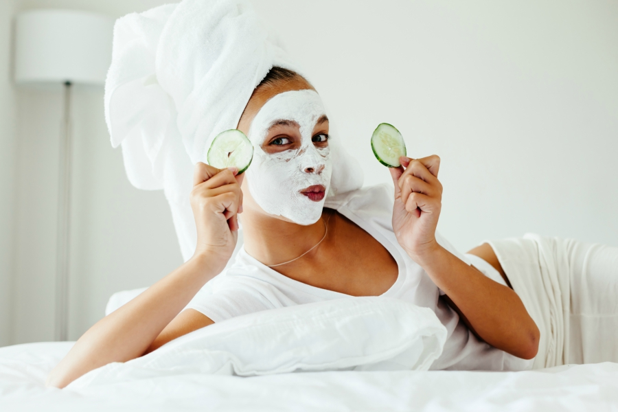 Teen girl with face mask and cucumbers