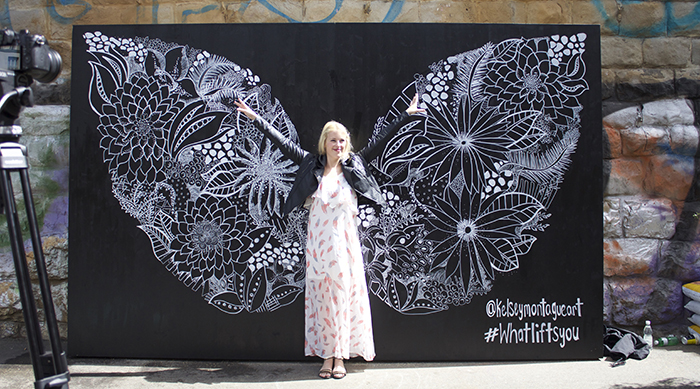Kelsey Montague standing in front of a pair of wings she painted onto a black wall
