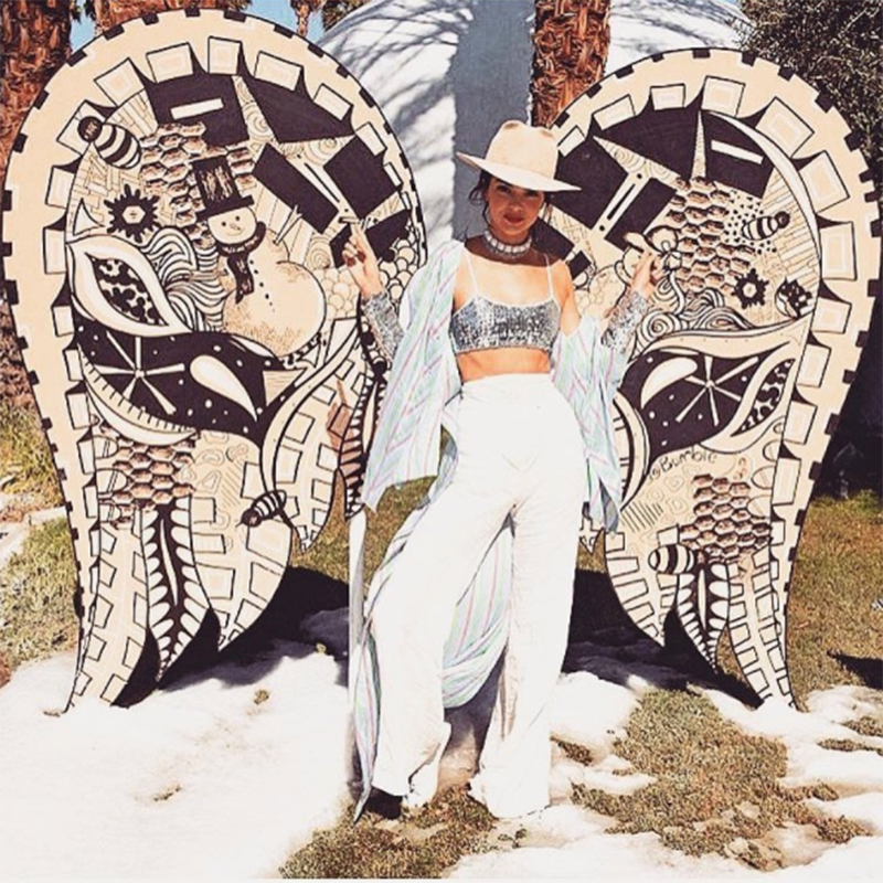 Kendall Jenner standing in front of a pair of angel wings