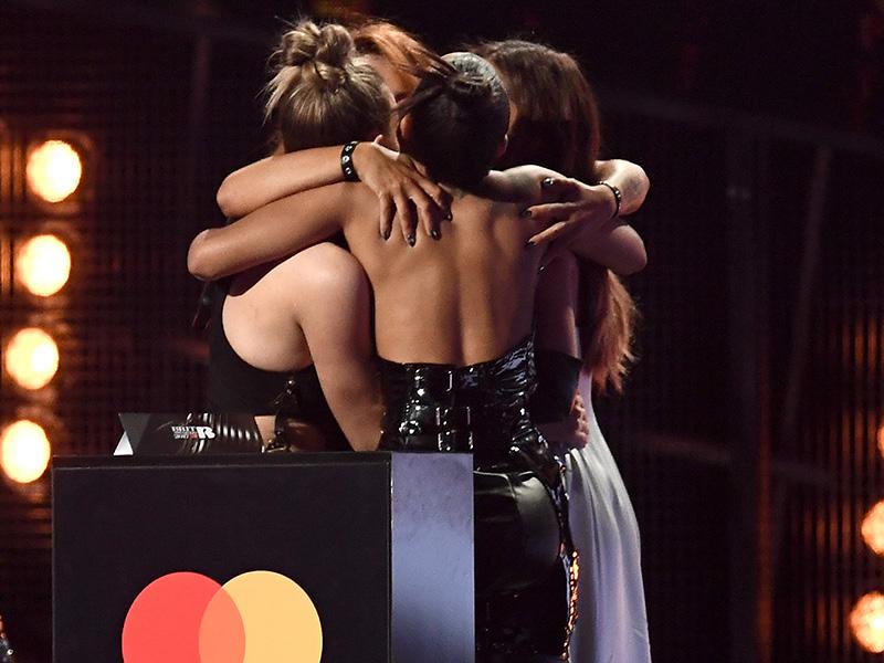 Little Mix hugging each other after winning a Brit Award