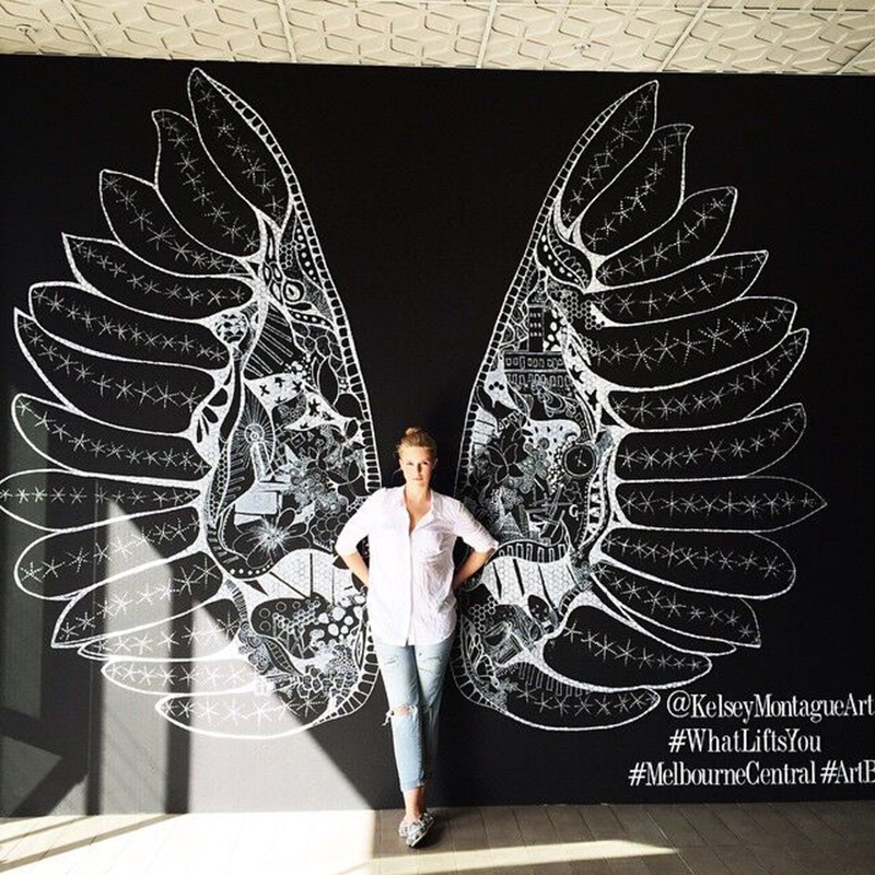 Girl posing in front of a black wall with white wings painted onto it