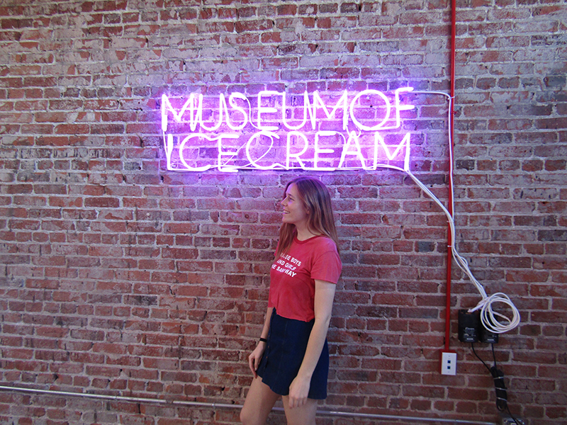 Girl standing underneath a neon sign reading Museum of Ice Cream